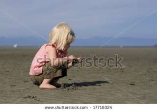 Cute Little Girl Crouched On On Beach Holding Sand In Her Hands. Stock